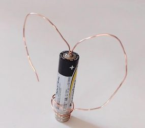 copper wire coiled into heart shape around AA battery balanced on two magnets