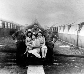 Soldiers and nurses posing for photo between Nissen huts