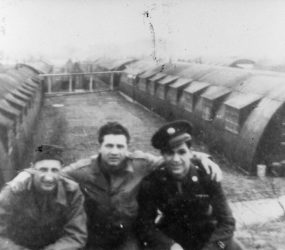 3 soldiers posing for photo between Nissen huts