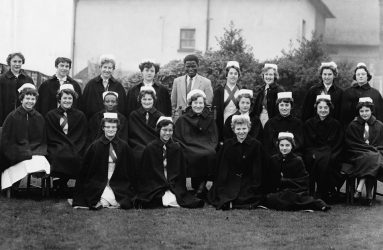 Student nurses pose for group photo in capes