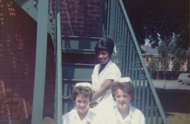 Three student nurses in uniform sitting on metal steps of nurses home