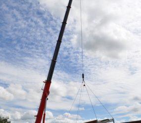 Crane lifting building into place