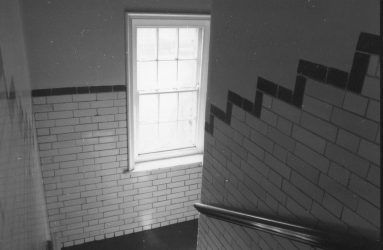 staircase with tiled walls, window and handrail down to tunnels