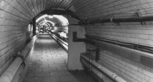 tiled tunnel with pipework visible
