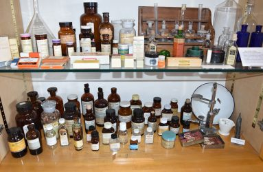 old pharmacy bottles in various sizes and mix of clear, brown, blue and green glass