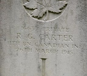 Close up of head stone with inscription and maple leaf