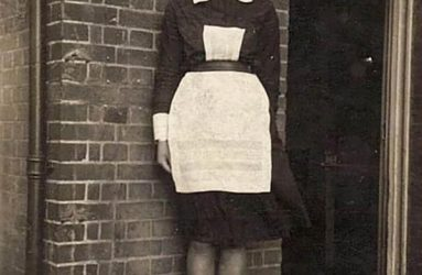 nurse standing outside brick building