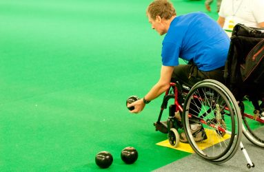man in wheelchair getting ready to bowl a ball