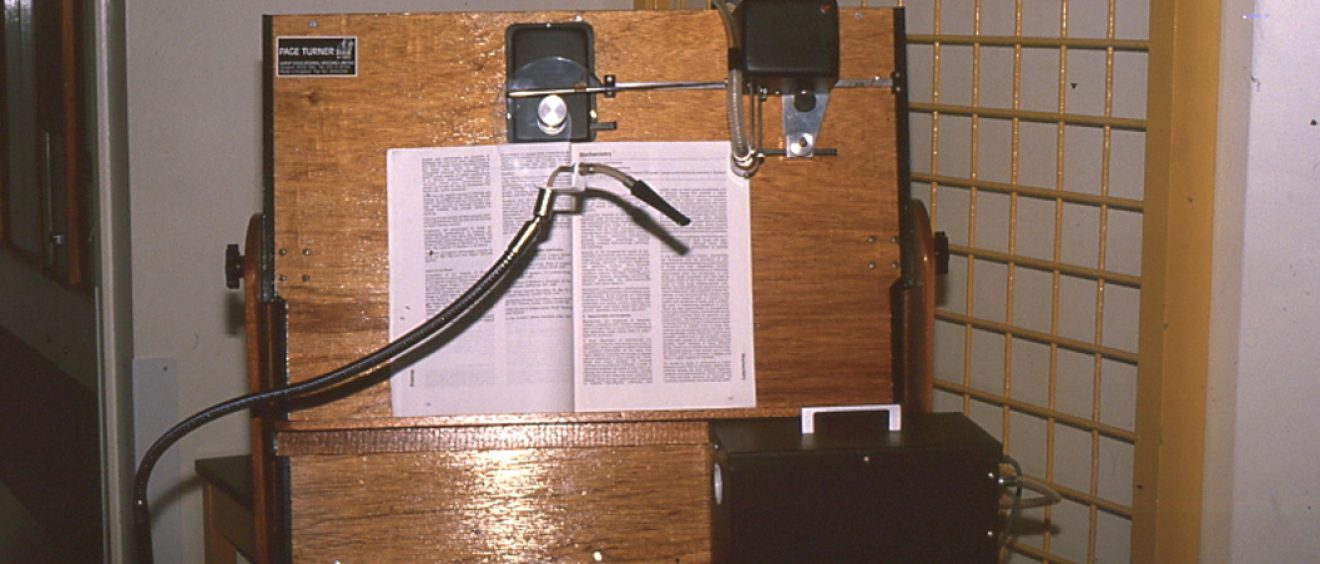 large wooden board holding a text book with tube attachment and device to turn the page