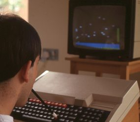 seated man with rubber ended pencil in mouth tapping on large keyboard attached to large TV screen monitor showing simple graphics