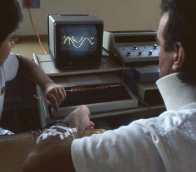 nurse sits with man who has wire attached to arm. large keyboard and a monitor display wavy line which patient is tracing alongside
