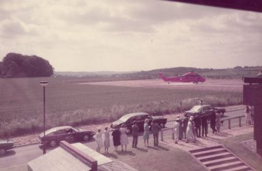 helicopter on landing site next to Spinal Unit, people waiting alongside the road