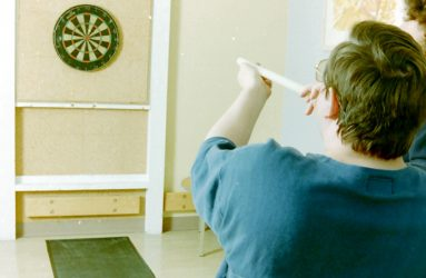 man in wheelchair blowing a pipe with dart aimed at dart board