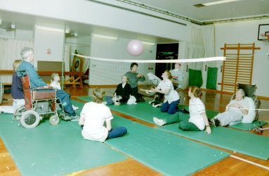 physiotherapists and occupational therapists sit on floor with patients some in wheelchairs, some on the floor playing volleyball in gym