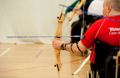 man in wheelchair drawing back bow preparing to shoot an arrow