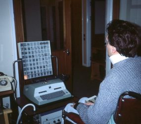 man in wheelchair in front of large typewriter device with a light box above it displaying letters and numbers in a grid
