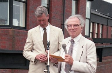 two men standing behind microphone, in front of the Spinal Unit building