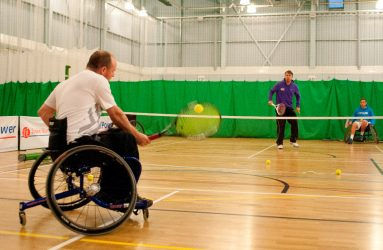 man in wheelchair playing tennis with a man who isn't