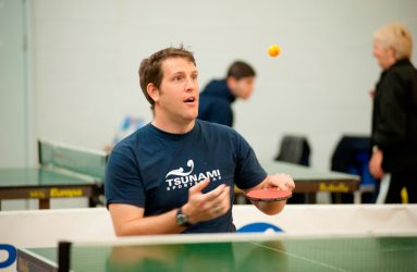 man playing table tennis, ball is captured mid air in the photo