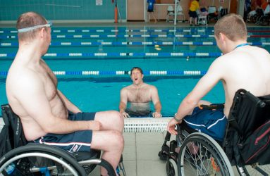 two men in wheelchairs at poolside looking at a third man in the pool hanging on to the side