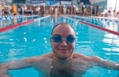 man wearing goggles looking straight to camera at end of pool