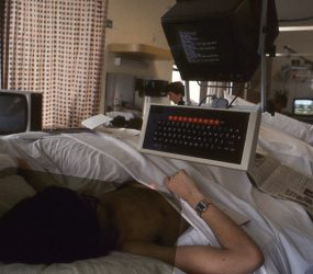 large box monitor and chunky keyboard suspended above patients bed