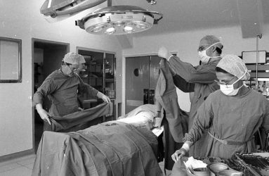 patient on table, doctors and nurses in scrubs preparing to operate