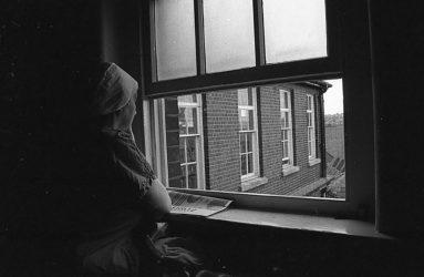 staff member in scrubs looking out of window