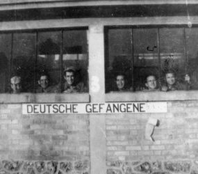Soldiers looking out of window with words 'DEUTSCHE GEFANGENE' underneath