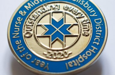 blue enamel badge with florence cross design and 'outstanding every time' inscription